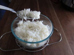 instant pot fluff rice with fork, rice in glass bowl on a metal rack