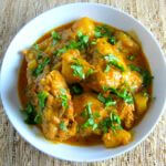 Indian Instant Pot Chicken Curry with cilantro in white bowl on straw placemant