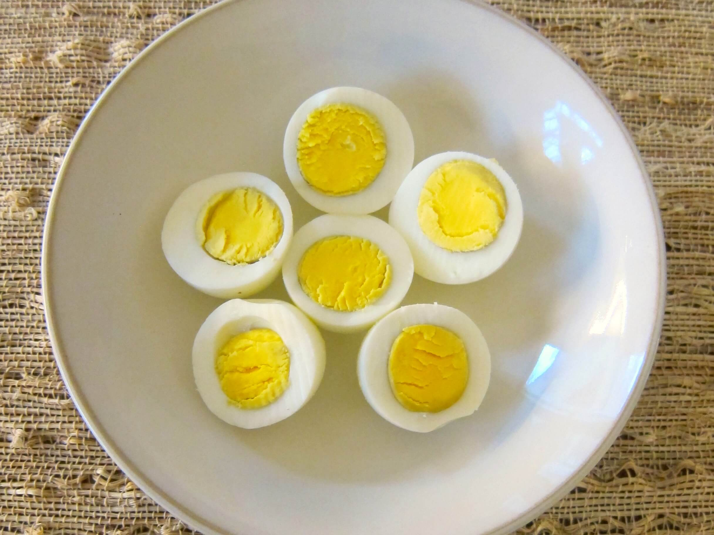 Three Instant Pot eggs cut into half in a white bowl, yellow side up