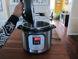 Instant Pot Manual - Water Test Complete - Instant Pot on wooden countertop showing Off and lid being removed