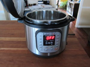Instant Pot Manual - Water Test Complete - Instant Pot on wooden countertop with lid propped open and display showing 'Off'