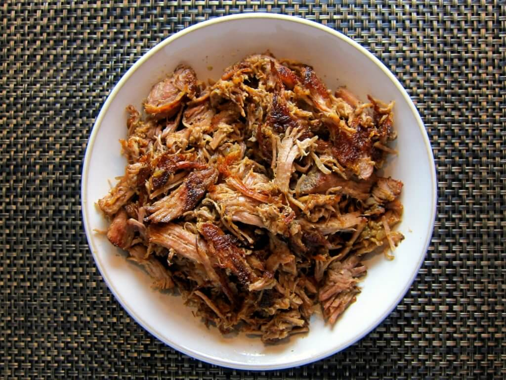 Instant Pot Carnitas - crispy and in white serving bowl on brown mat - Paint the Kitchen Red