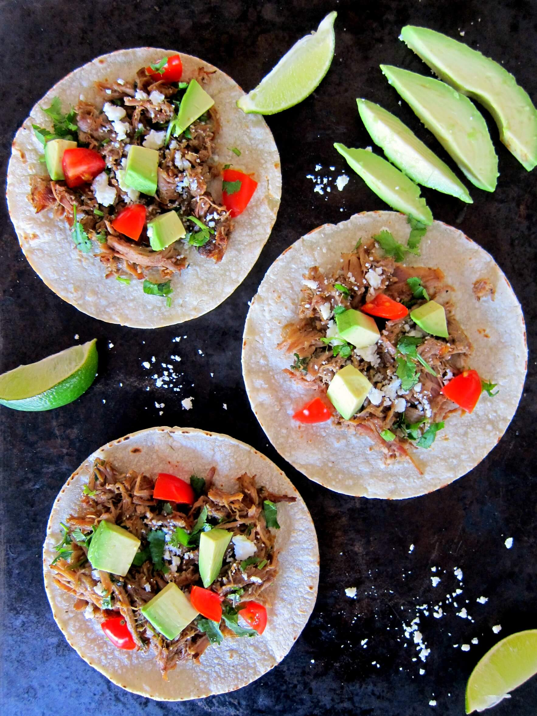 Instant Pot Carnitas open tacos topped with avocados and tomatoes on a black background - Paint the Kitchen Red