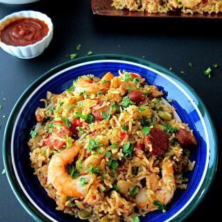 Instant Pot Jambalaya in blue bowl with hot sauce, stack of plates in background on a black table - Paint the Kitchen Red