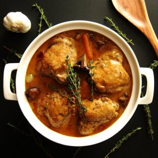 Instant Pot Coq Au Vin P1 - chicken and carrots in gravy in a large white pot with thyme sprigs sprinkled on top - Paint the Kitchen Red