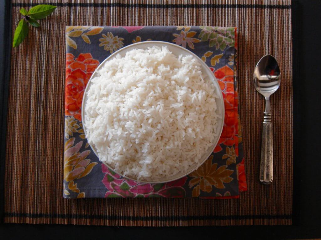 Instant Pot Jasmine Rice in white bowl on colorful flowery napkin on straw placemat with thai basil leaves and spoon- Paint the Kitchen Red