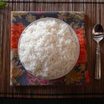 Instant Pot Jasmine Rice in white bowl on straw placemat with colorful napkin and a spoon - Paint the Kitchen Red