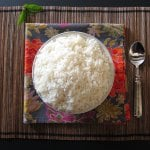 Instant Pot Jasmine Rice in white bowl on flowery colorful napkin and straw placemat with a spoon- Paint the Kitchen Red