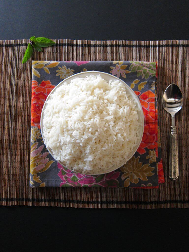 Instant Pot Jasmine Rice in white bowl on straw placemat, on a colorful flowery napkin with spoon - Paint the Kitchen Red
