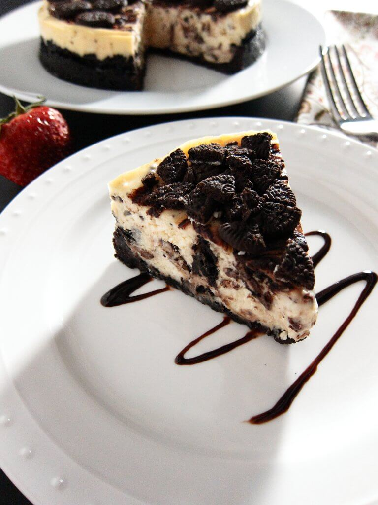 Instant Pot Oreo Cheesecake slice with remaining cake in background - Paint the Kitchen Red