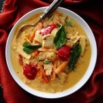 Instant Pot Thai Red Curry with colorful vegetables in white bowl with spoon on rich red napkin. From Paint the Kitchen Red
