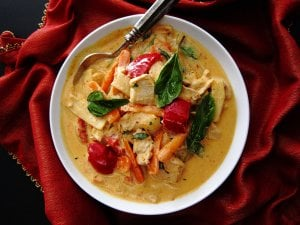 Instant Pot Thai Red Curry with colorful vegetables in white bowl with spoon on rich red napkin.
