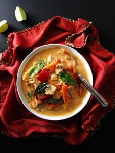 Instant Pot Thai Red Curry Chicken on red napkin with gold and two pieces of lime on black surface - Paint the Kitchen Red