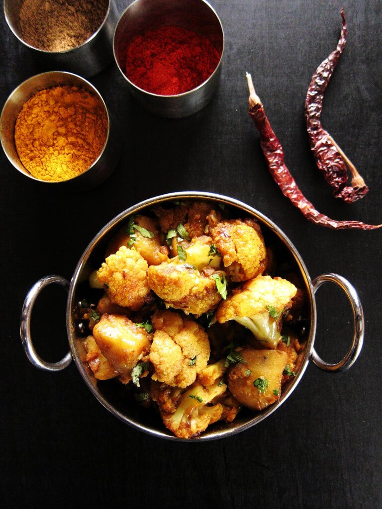 Instant Pot Aloo Gobi | Indian Cauliflower and potatoes with cilantro in metal bowl with bowls of Indian spices in the background - Paint the Kitchen Red
