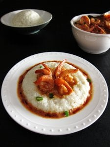 Instant Pot Shrimp and Grits on white plate, black table with rice and shrimp in bowls in the background - Paint the Kitchen Red