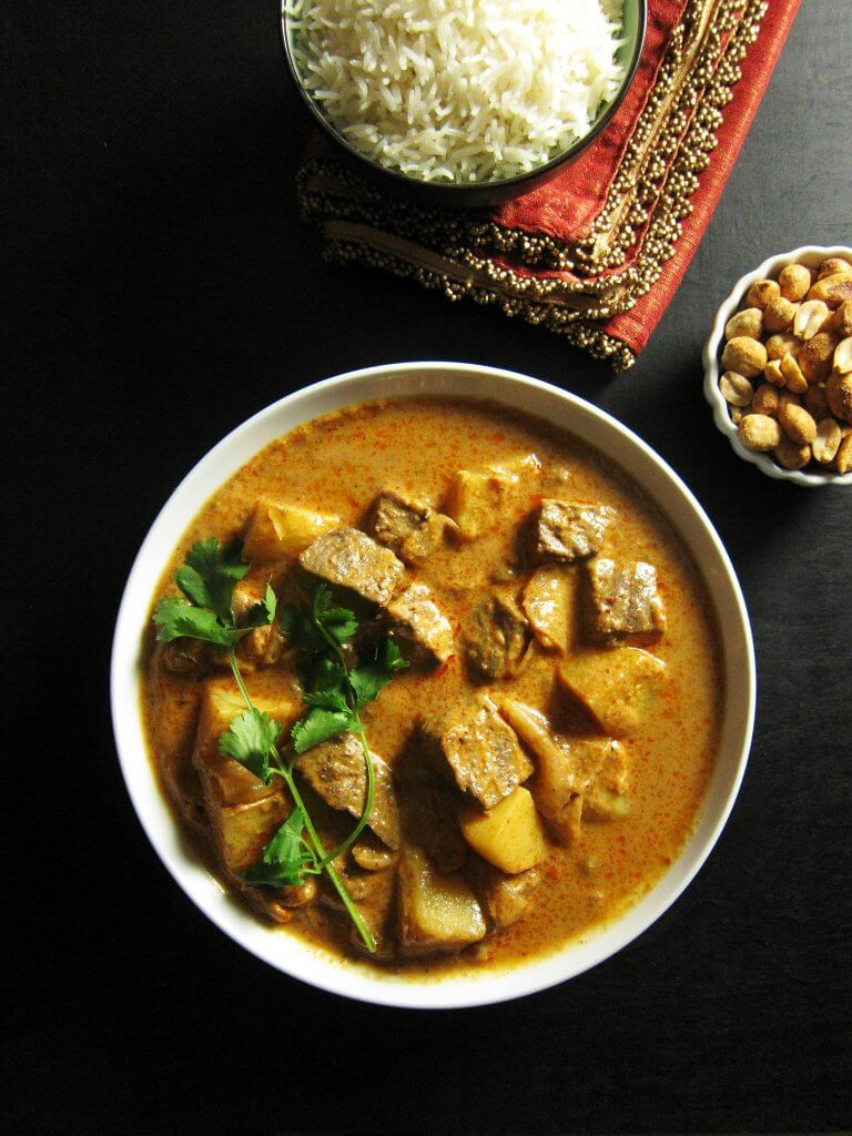 Instant Pot Massaman Curry with Beef, potatoes, garnished with cilantro in white bowl with rice and peanuts in background - Paint the Kitchen Red