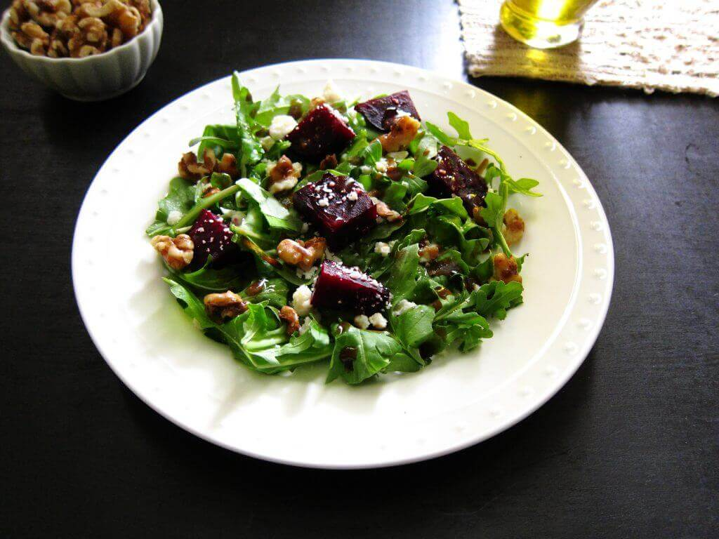 Instant Pot beet, arugula, candied walnut salad on white plate with walnuts in bowl in background