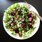 Instant Pot beet, arugula, candied walnut salad on white plate with fork or dark background