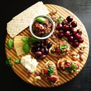 Instant Pot Ratatouille - round wooden board with cheeses, basil, olives, crostini, cherries, nuts, crackers