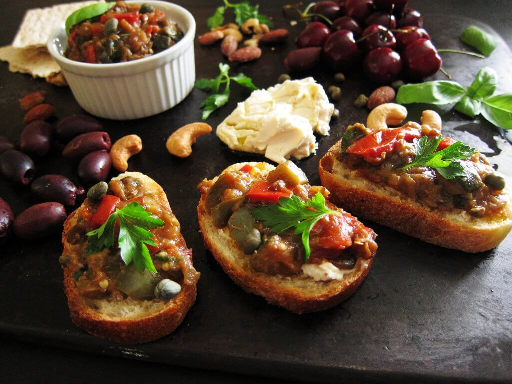 Instant Pot Ratatouille on crostini with cheese, nuts, olives, cherries, basil leaves on a dark background - Paint the Kitchen Red