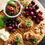 Instant Pot Ratatouille in a bowl and on crusty bread, all on a round wooden board with cherries, cheese, nuts