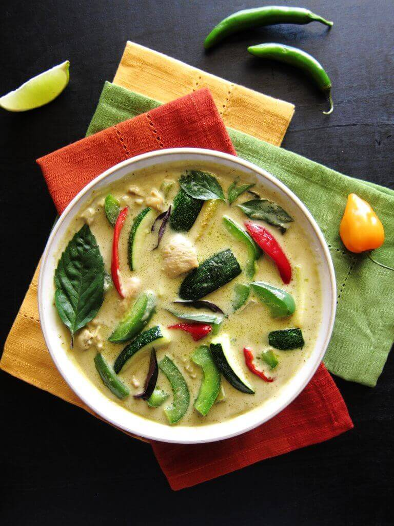 Instant Pot Thai Green Curry with Chicken with colorful green curry in white bowl on three colorful napkins. With lime slice and chilies on a black background- Paint the Kitchen Red