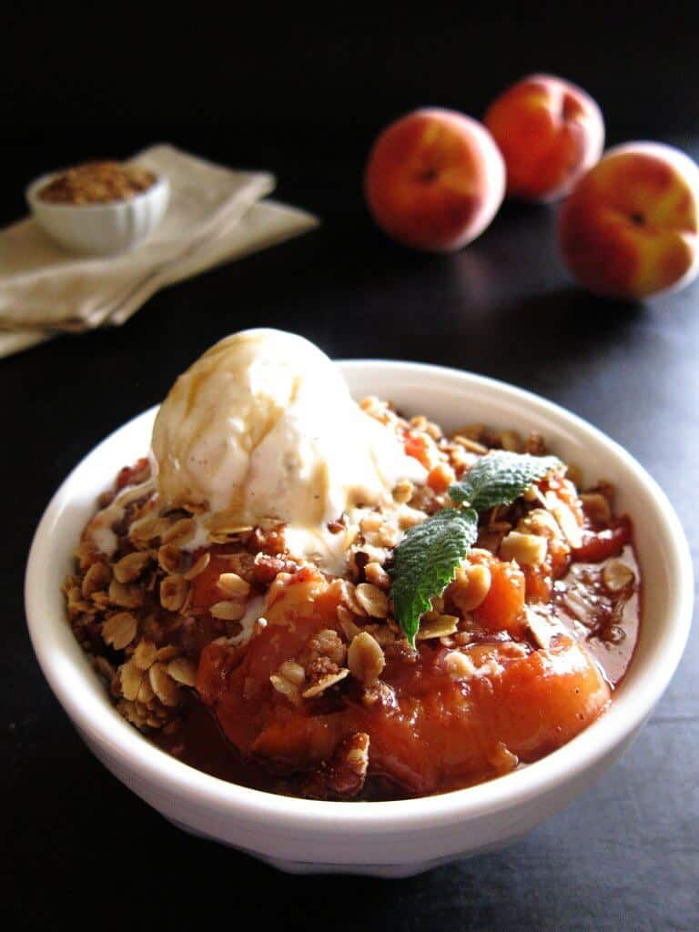 Instant Pot Peach Crisp in white bowl with scoop of vanilla ice cream and garnished with mint - Paint the Kitchen Red