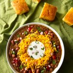 Instant Pot Chili in white bowl on green cloth with cornbread; topped with cheese, sour cream and green onions - Paint the Kitchen Red