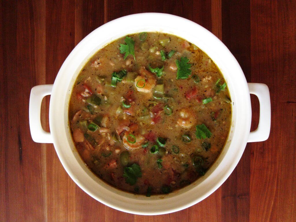 Instant Pot Gumbo topped with green onions in large white pot with handles on wooden background- Paint the Kitchen Red