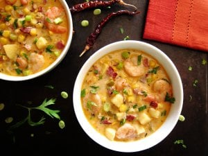 Creamy Instant Pot Chipotle Shrimp Soup colorful with red napkin, dried red chili peppers, parsley and green onions sprinkled on black background - Paint the Kitchen Red