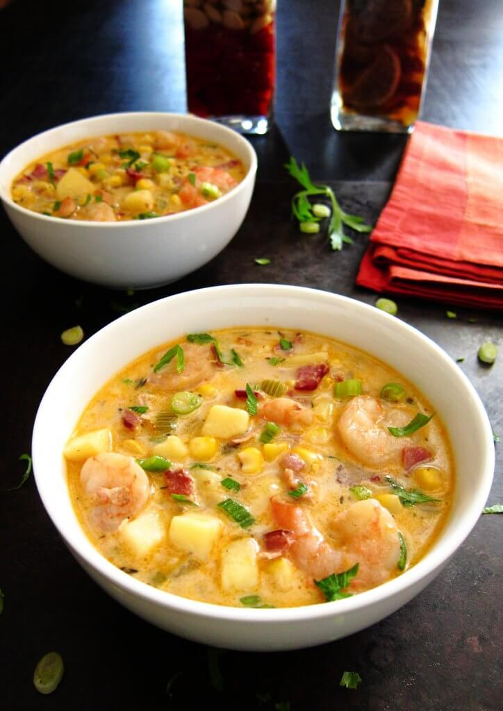 Two white bowls of colorful Creamy Instant Pot Chipotle Shrimp Soup with potatoes, corn, bacon and green onions on black background - Paint the Kitchen Red