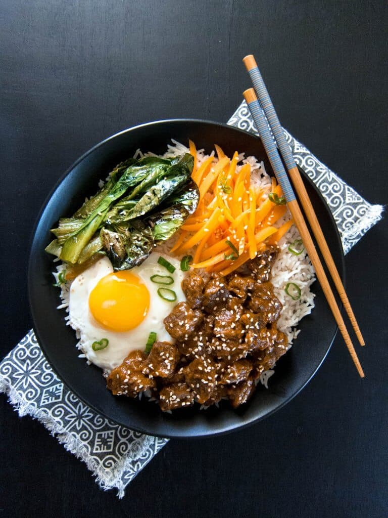Instant Pot Korean Beef in black bowl with carrots, fried egg, baby bok choy on a black and white napkin and chopsticks on the bowl on black background - Paint the Kitchen Red