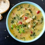 Instant Pot Chicken Curry Soup - yellow colored soup topped with cilantro in teal bowl on black background with french bread slices - Paint the Kitchen Red