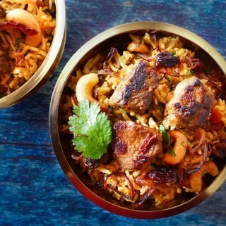 Instant Pot Biryani with Lamb landscape with 2 brass bowls on blue table - Paint the Kitchen Red