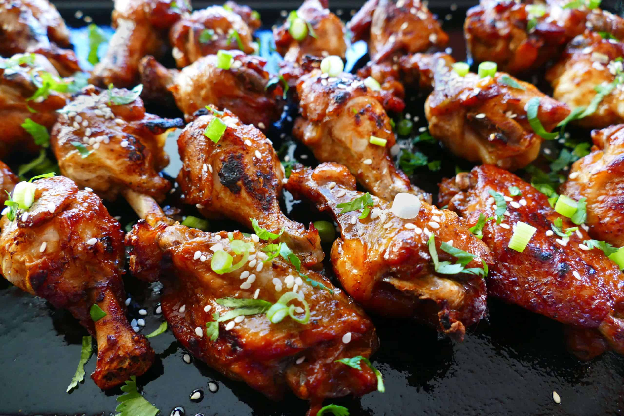 Instant Pot Teriyaki Wings cooked on dark background with green onions and sesame seeds sprinkled on top - Paint the Kitchen Red