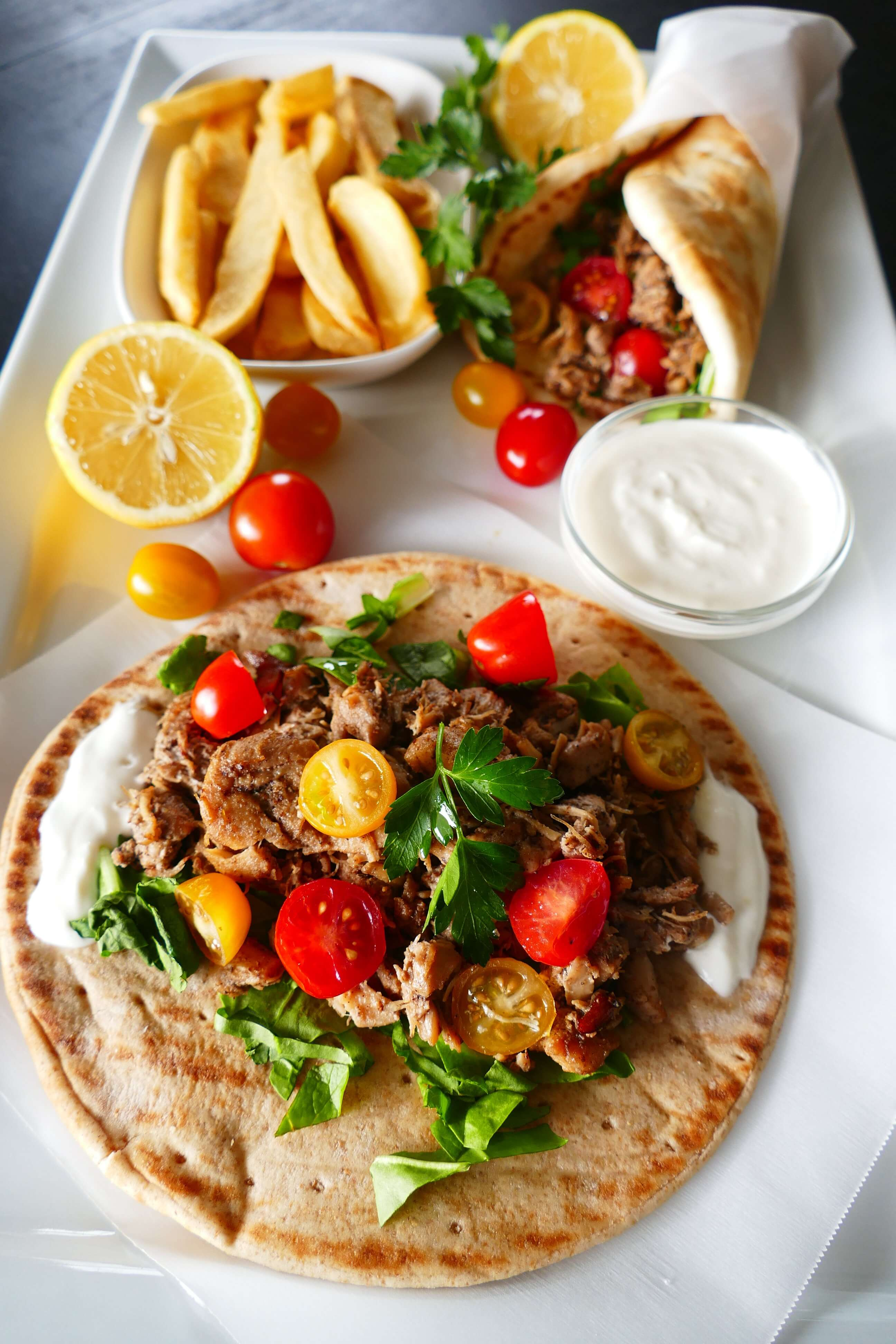 Instant Pot Chicken Shawarma - pita with white sauce, chicken, salad greens, halved cherry yellow and red tomatoes on parchment placed on a large white plate with French fries and white sauce and folded shawarma