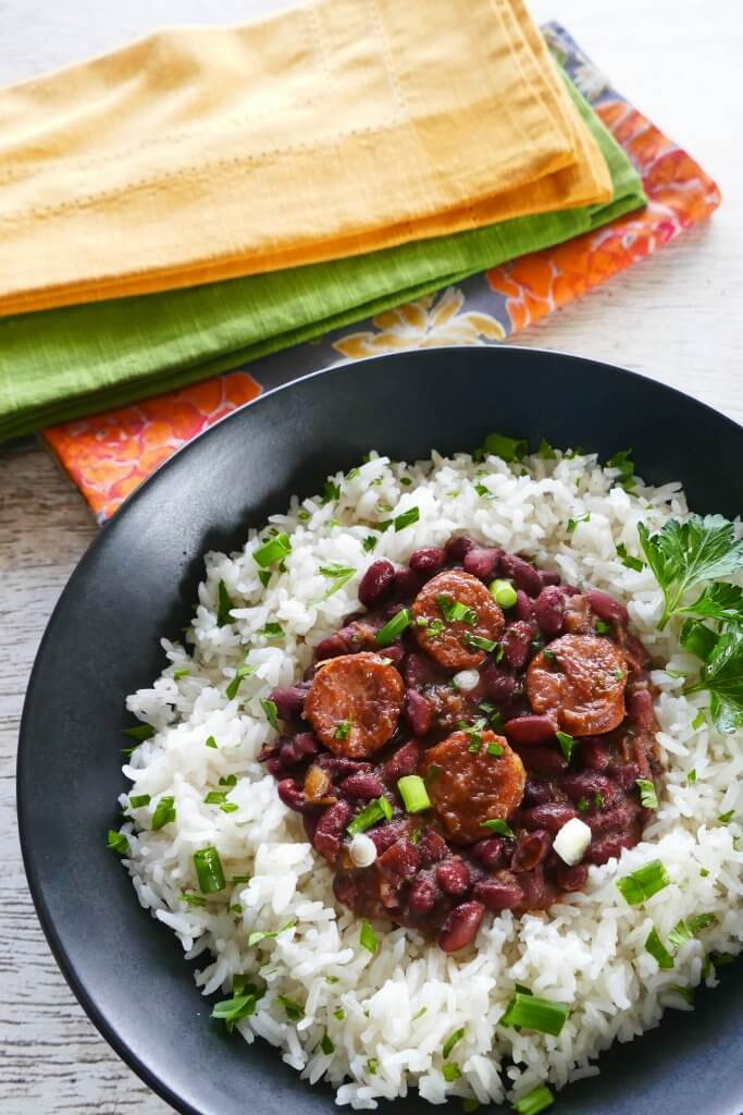 Instant Pot Red Beans and Sausage served on rice in a black bowl on a white wooden background with multicolor napkins. Garnished with parsley and green onions - Paint the Kitchen Red