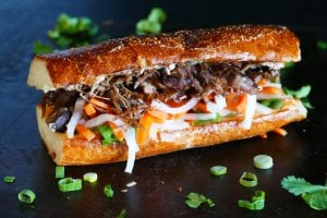 Instant Pot Banh Mi sandwich on black background, with meat, daikon, carrots and cilantro; cilantro and green onions sprinkled on surface - Paint the Kitchen Red