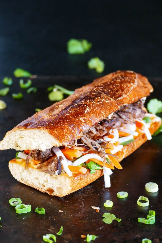 Instant Pot Banh Mi sandwich portrait on black background, with meat, daikon, carrots and cilantro; cilantro and green onions sprinkled on surface - Paint the Kitchen Red