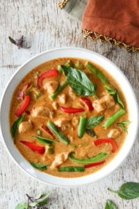Instant Pot Panang Curry with chicken, green beans, red and green peppers, Thai basil in a white bowl on a light wood background