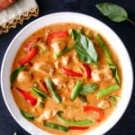 Instant Pot Panang Curry with chicken, green beans, red and green peppers, Thai basil in a white bowl on a black background