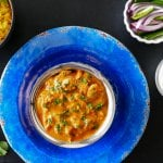 Instant Pot Chicken Tikka Masala in bowl on bright blue plate, with yellow rice, red onions and green chilis and yogurt (raita) in bowls in background - Paint the Kitchen Red