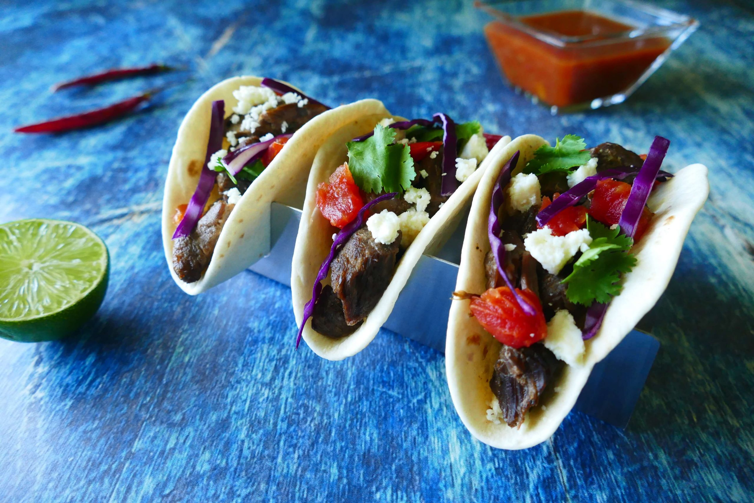 Instant Pot Carne Asada - three tacos with purple cabbage, tomatoes, cheese, cilantro on a blue background with salsa, red chilis and cut lime