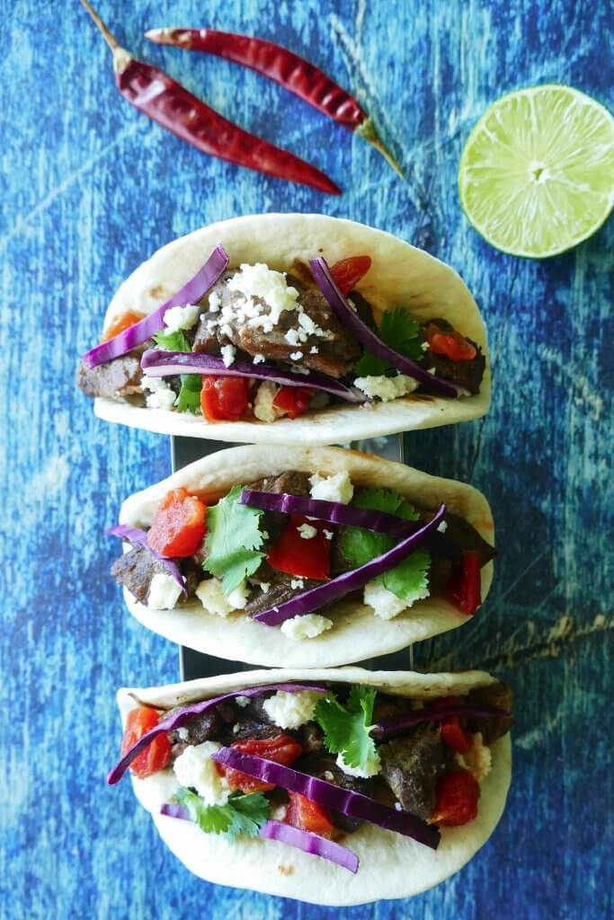 Instant Pot Carne Asada - three tacos with purple cabbage, tomatoes, cheese on a blue background with red chilis and cut lime