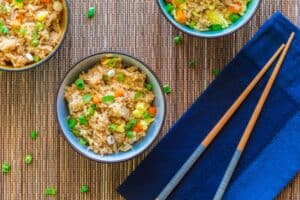 Instant Pot Fried Rice - bowl of rice with vegetables garnished with green onions in blue bowl on blue napkin with chopsticks