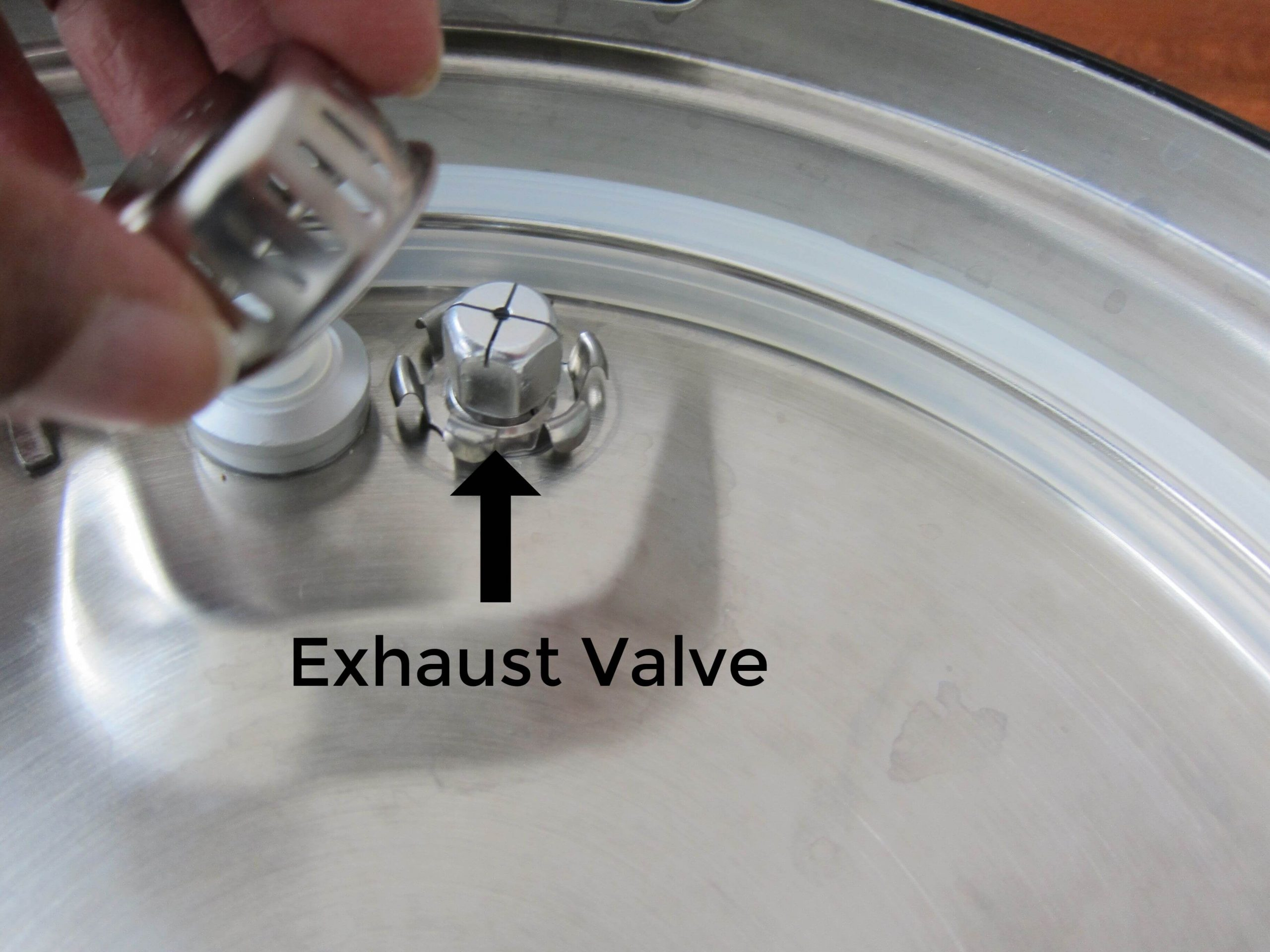 instant pot lid with anti-block shield being removed and arrow pointing to exhaust valve