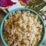 Instant Pot Brown Rice P1 turquoise bowl with brown rice with flowered napkin in background - Paint the Kitchen Red