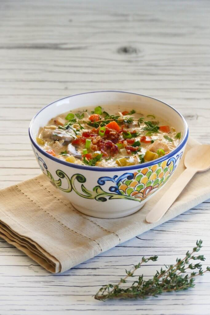 Instant Pot Cream of Chicken Soup in flower painted bowl garnished with bacon bits and scallions, napkin and fresh thyme in background