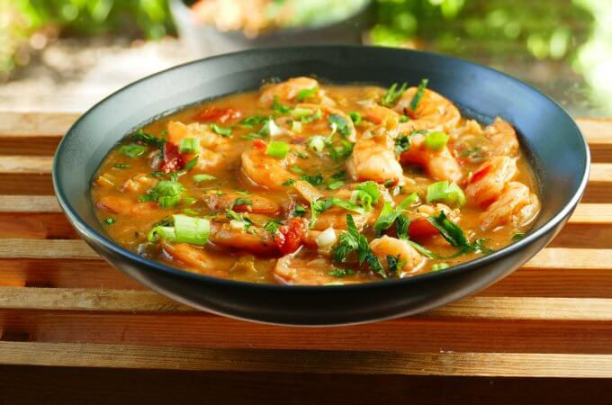 Instant Pot Shrimp Etouffee garnished with green onions and chopped parsley in black bowl on a wood slat background - Paint the Kitchen Red