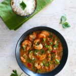 Instant Pot Shrimp Etouffee garnished with green onions and chopped parsley in black bowl with rice in a bowl on a green napkin - Paint the Kitchen Red